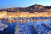 France, Bouches du Rhone, Marseille, Vieux Port at nightfall with the Basilica Notre Dame de la Garde at the bottom