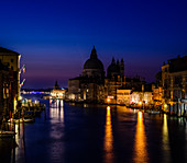 The Grand Canal in Venice, at night, historic buildings in silhouette.