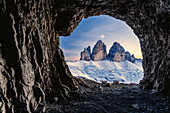 Tre Cime di Lavaredo lit by moon seen from opening in rocks of a war cave, Sesto Dolomites, Trentino-Alto Adige, Italy, Europe