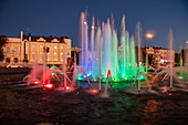 Illuminated music fountain along promenade on the bank of Volga River at dusk, Astrakhan, Astrakhan District, Russia, Europe