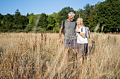 Smiling mature couple hiking in forest