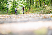 Portrait of smiling mature couple riding bicycles in forest