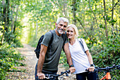 Portrait of smiling mature couple with bicycles standing in forest