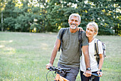 Portrait of smiling mature couple with bicycle standing in forest