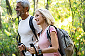 Smiling mature couple hiking together in forest