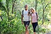 Smiling mature woman showing direction to her husband while hiking in forest