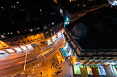 Overhead view of pedestrians and traffic on street at night