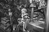 Little boy sits on an old tractor and steers, black and white, Allgäu, Bavaria
