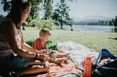 Mother is sitting by the lake with her son on a beautiful summer day and eating an ice cream. Family, summer day, sunshine, lake, Allgäu, Bavaria
