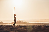 pregnant woman standing with surfboard on the beach, surfing, pregnancy, Portugal