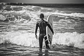 Surfer stands with surfboard on the beach, surfing, vacation, Portugal