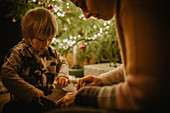 little boy unwraps his gifts in front of the Christmas tree, Christmas, family