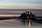 Blick am Abend auf die felsige Insel Mont Saint Michel mit dem gleichnamigen Kloster, Normandie, Frankreich.