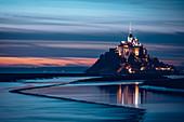Blick am Abend auf die felsige Insel Mont Saint Michel mit dem gleichnamigen Kloster, Normandie, Frankreich
