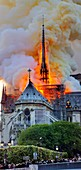 France, Paris, area listed as World Heritage by UNESCO, Notre Dame Cathedral of 14th century Gothic architecture during the fire of 15th April 2019, fire spreading in the arrow the frame of the transept and the roof of the nave, thick yellow smoke coming from the burning of the lead roof