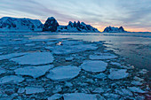 Sunrise on snow-covered mountains and dense sea ice in Neumayer Channel, Palmer Archipelago, Antarctica, Polar Regions