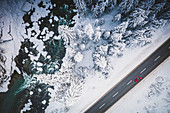 Car traveling on the snowy mountain road on side of frozen river and woods, aerial view, Switzerland, Europe