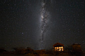 South hemisphere Milky Way and a small illuminated hut, Namibia, Africa