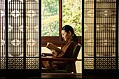 Serene young woman reading book behind patterned shoji doors