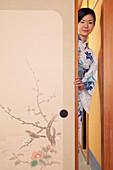Portrait beautiful young woman in kimono behind painted door