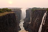 Victoria Falls, huge waterfalls of the Zambezi river flowing over sheer cliffs.