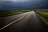 USA,South Dakota,Badlands National Park,Storm clouds over road in prairie