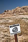 USA,South Dakota,Badlands National Park,Beware of Rattlesnakes sign in Badlands National Park