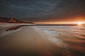 Poland,Pomerania,Leba,Baltic Sea coastline with distant town at sunset