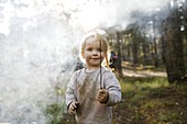 Portrait of girl (2-3) holding marshmallow near campfire in forest,Wasatch Cache National Forest