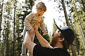Father holding smiling daughter (2-3) in forest,Wasatch-Cache National Forest