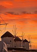 Greece,Cyclades Islands,Mykonos,Chora,Whitewashed windmills against sunset sky