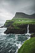 Denmark,Faroe Islands,Gasadalur Village,M?Lafossur Waterfall,Coastline with Mulafossur Waterfall falling into Atlantic Ocean