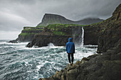 Denmark,Faroe Islands,Gasadalur Village,M?Lafossur Waterfall,Man standing on cliff and looking at Mulafossur Waterfall day during storm