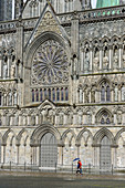 People with umbrella in front of Nidaros Cathedral west facade, Trondheim, Norway