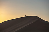 Silhouette von Menschen auf Sanddüne außerhalb Arabian Nights Village Wüstenresort bei Sonnenuntergang, Arabian Nights Village, Razeen Area of Al Khatim, Abu Dhabi, Vereinigte Arabische Emirate, Emirate, Naher Osten