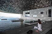 Woman admires architecture of the Louvre Abu Dhabi Museum, Abu Dhabi, Abu Dhabi, United Arab Emirates, Middle East