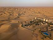 Aerial view of Arabian Nights Village desert resort amidst dunes, Arabian Nights Village, Razeen Area of Al Khatim, Abu Dhabi, United Arab Emirates, Middle East