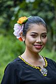 Porträt einer fröhlichen jungen Frau in traditioneller Tracht im Sarawak Cultural Village, near Kuching, Sarawak, Borneo, Malaysia, Asien
