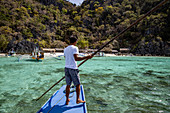 Bootsmann auf traditionellem philippinischen Banca Auslegerkanu beim Dicantuman Beach auf der Insel Coron, Banuang Daan, Coron, Palawan, Philippinen, Asien