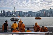 Mönche auf der Tsim Sha Tsui-Seite des Victoria Harbour mit der Skyline von Hongkong in der Ferne, Hongkong, Hongkong, China, Asien