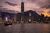 Kowloon Fähre überquert Victoria Harbour mit der Skyline von Hongkong in der Ferne bei Sonnenuntergang, Hongkong, Hongkong, China, Asien
