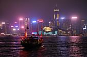 Traditionelle Dschunke die als Touristen Sightseeing-Boot dient im Victoria Harbour mit Skyline von Hongkong dahinter bei Nacht, Hongkong, Hongkong, China, Asien