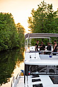 People enjoy wine aboard a Le Boat Horizon houseboat docked at Beveridge Locks along the River Tay River at sunset, near Lower Rideau Lake, Ontario, Canada, North America