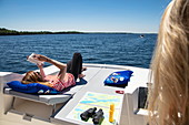 Young woman relaxes on the sundeck of a Le Boat Horizon houseboat and reads a book, Lower Rideau Lake, Ontario, Canada, North America