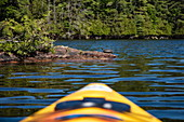 Tip of a yellow kayak with turtle resting on ledge at Indian Lake, near Chaffey's Lock, Ontario, Canada, North America