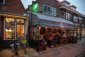 Menschen sitzen draußen und genießen Bier im Cafe de Zeevaart in der Abenddämmerung, West Terschelling, Terschelling, Westfriesische Inseln, Friesland, Niederlande, Europa