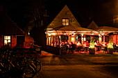 Menschen sitzen draußen und genießen Abendessen im Restaurant Rixt bei Nacht, Nes, Ameland, Westfriesische Inseln, Friesland, Niederlande, Europa