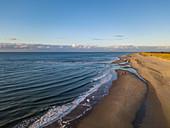 Luftaufnahme von drei Menschen, die auf galoppierenden Pferden am Strand in der Nähe der Westerduinen-Dünen entlang der Nordseeküste bei Sonnenuntergang reiten, nahe Den Hoorn, Texel, Westfriesische Inseln, Friesland, Niederlande, Europa
