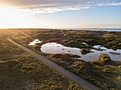 Luftaufnahme von Mann auf Fahrrad der an Seen und Dünen entlang der Nordseeküste bei Sonnenuntergang radelt, Midsland aan Zee, Terschelling, Westfriesische Inseln, Friesland, Niederlande, Europa
