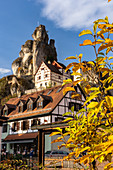 View of houses in front of rocks in Tüchersfeld with autumn leaves in the foreground, Upper Franconia, Bavaria, Germany